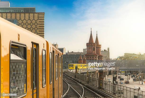 subway train on railroad tracks by oberbaumbruecke against sky - berlin stock pictures, royalty-free photos & images