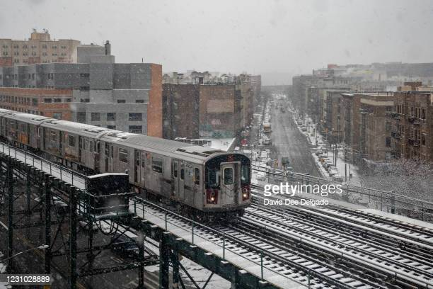 Subway train travels on the elevated track over the snow covered streets on February 7, 2021 in Bronx borough of New York City. The second snowstorm...