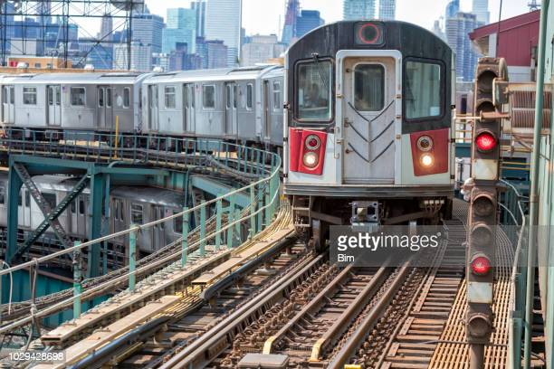 subway trains speeding on elevated track in queens, new york - queens new york city stock pictures, royalty-free photos & images