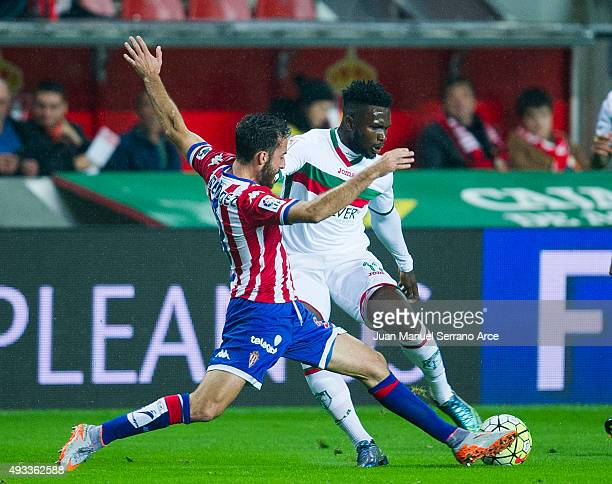 Success Ajayi Isaac of Granada CF duels for the ball with Alex Menendez of Real Sporting de Gijon during the La Liga match between Real Sporting de...