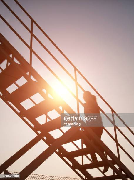 Success concept with people silhouette climbing stairs in the sunset
