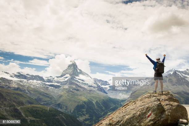 Success - male hiker stands on a rock