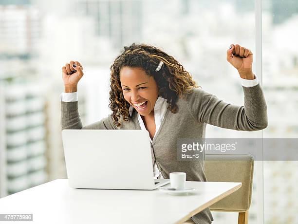 Succès afro-américain de femme d'affaires avec ordinateur dans le bureau.