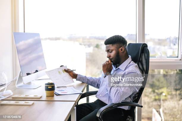 successful african businessman working on computer in his office. - financial occupation stock pictures, royalty-free photos & images