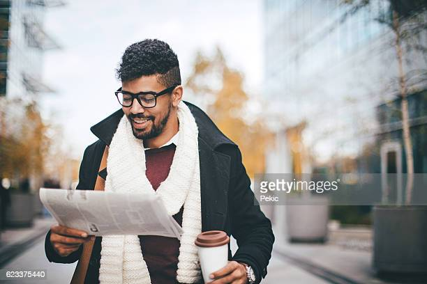 Successful african man reading a newspaper while drinking coffee