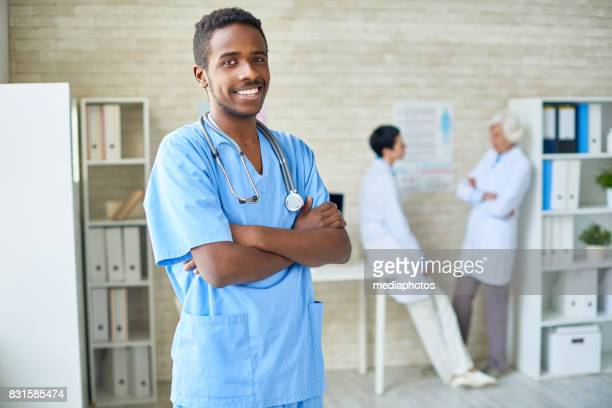 successful african surgeon in doctors office - male nurse stock pictures, royalty-free photos & images