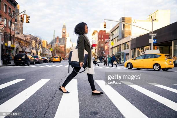 successful and elegant woman walks the streets of new york - strisce pedonali foto e immagini stock