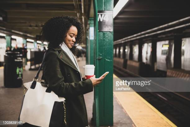 successful and elegant woman walks the streets of new york - new york city subway stock pictures, royalty-free photos & images