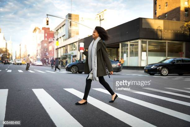 successful and elegant woman walks the streets of new york - pedestrian crossing stock photos and pictures