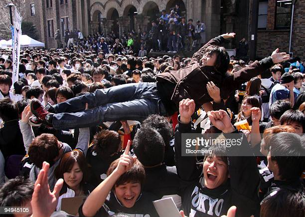 A successful applicant is tossed in the air by current students at The University of Tokyo in Tokyo Japan on Tuesday March 10 2009 The University of...
