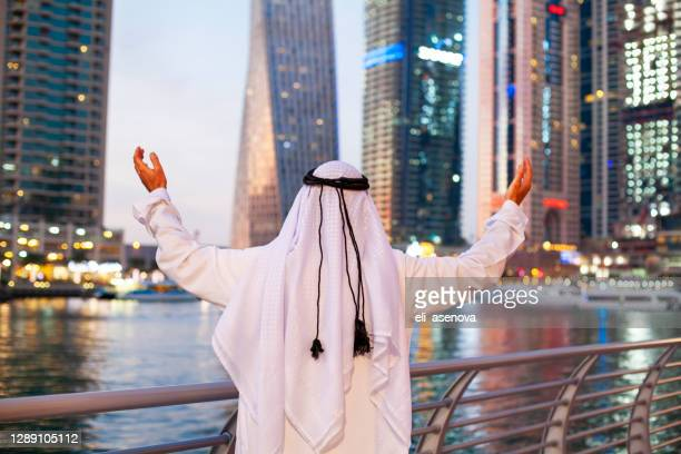 successful arabian sheikh businessman against the skyscraper in dubai marina - gesturing stock pictures, royalty-free photos & images
