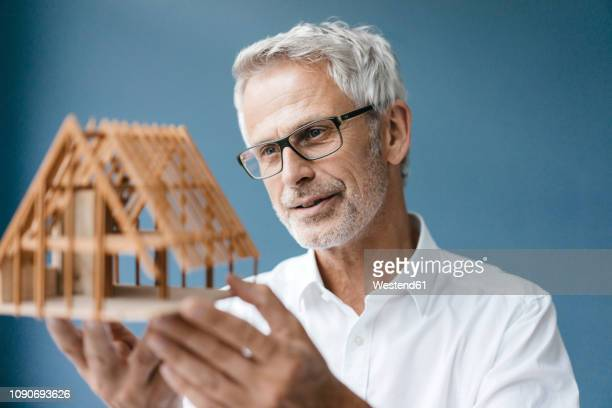 successful architect looking at model of a house - geschäftskleidung stock-fotos und bilder