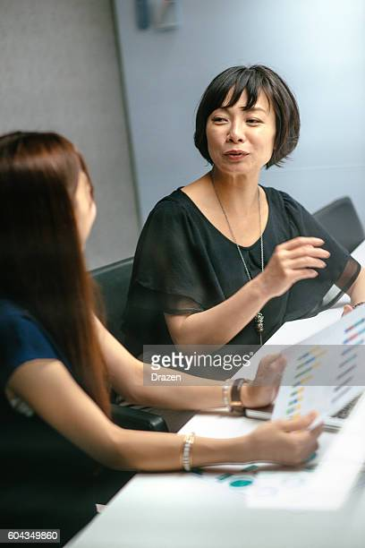 Successful Asian businesswomen preparing reports for board of directors