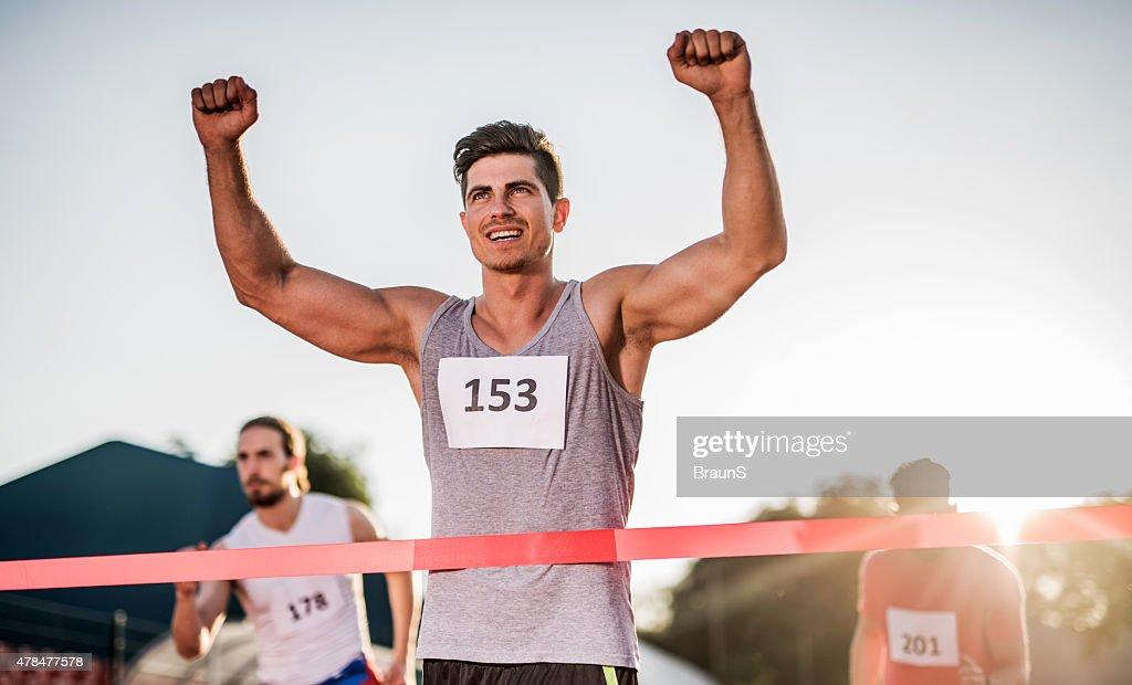Erfolgreiche Sportlerin Überqueren der Ziellinie und gewinnt das Rennen. : Stock-Foto