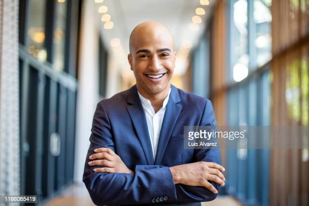 successful bald businessman in hotel corridor - launch event stock-fotos und bilder