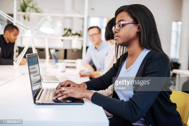 successful black businesswoman working in scandinavian company. - hot desking stock pictures, royalty-free photos & images