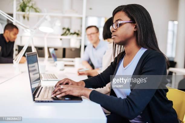 femme d'affaires noire réussie travaillant dans la compagnie scandinave. - hot desking photos et images de collection