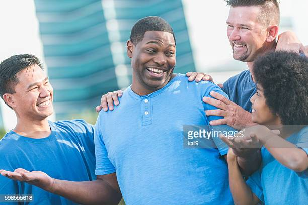 successful black man getting pat on back from friends - adulation stock pictures, royalty-free photos & images