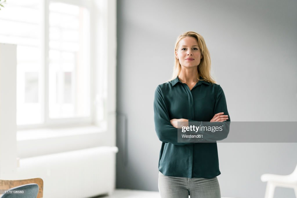 Successful, blond businesswoman standing in bright room, with arms crossed : Stock-Foto