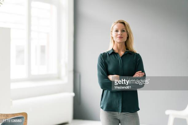 successful, blond businesswoman standing in bright room, with arms crossed - entschlossenheit stock-fotos und bilder
