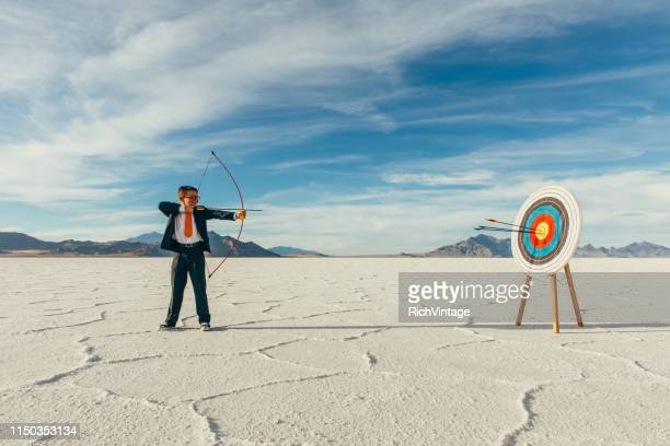 successful business boy with arrows in target - sports target stock pictures, royalty-free photos & images