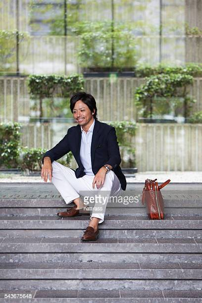 Successful business man sitting on the steps