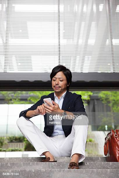 Successful business man sitting on the steps working on phone