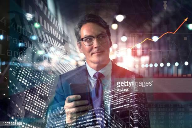 erfolgreicher geschäftsmann, der mit seinem handy am globalen aktienmarkt arbeitet - börsenhändler stock-fotos und bilder