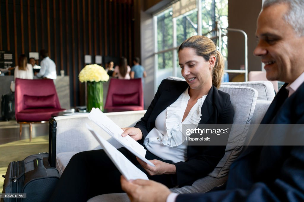 Successful business partners in a meeting at hotel lounge checking some documents : Stock Photo