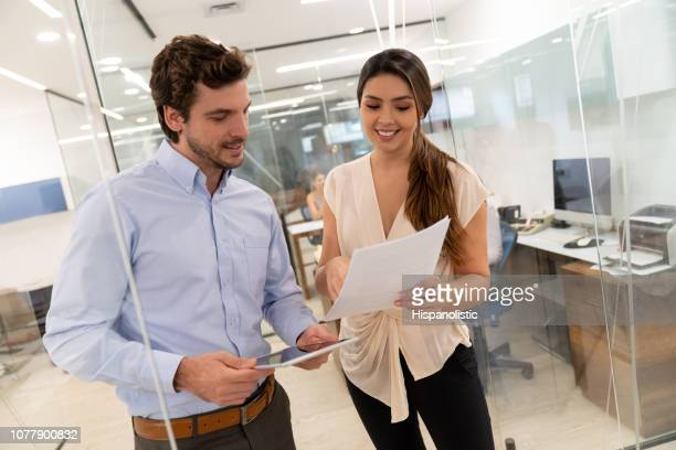 successful business partners looking at a document and tablet while discussing something standing at the corridor's office both smiling - hispanolistic stock photos and pictures