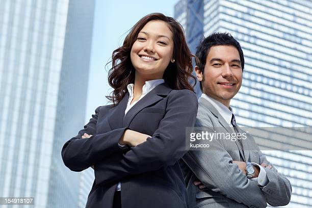 Erfolgreiche Geschäftsleute vor modernen Bürogebäude