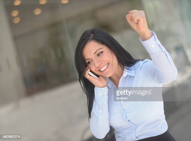 Successful business woman on the phone looking excited