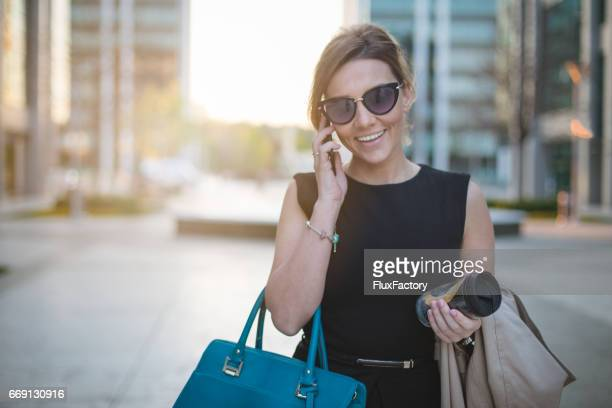 Successful business woman smiling on the phone and holding coffee