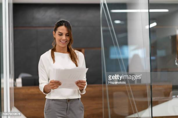 Successful business young female looking at some documents at the office very happy