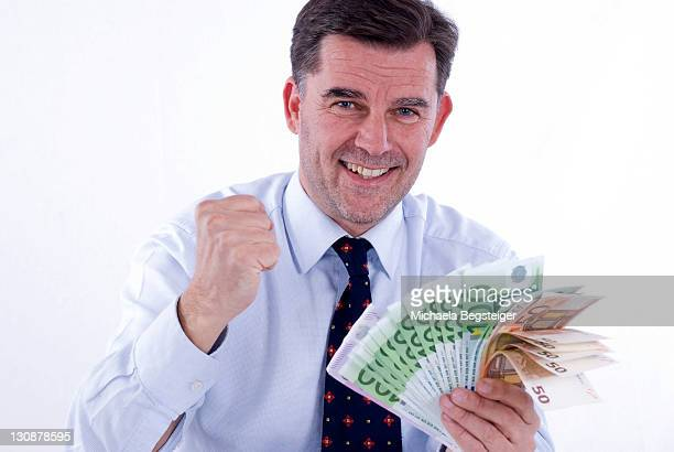 Successful businessman, 50 +, holding banknotes