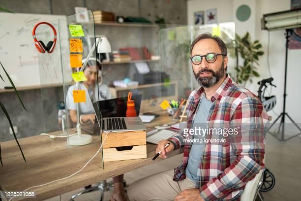 中小企業のオフィスで成功したビジネスマン - チェックシャツ ストックフォトと画像