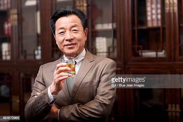 successful businessman enjoying wine - 中国北東部 ストックフォトと画像