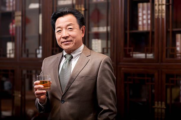 successful businessman enjoying wine - old asian man drinking wine stock pictures, royalty-free photos & images