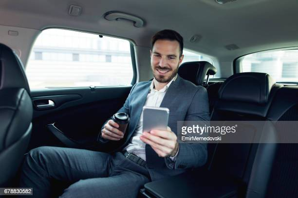 Homme d'affaires prospère dans une voiture et la messagerie texte.