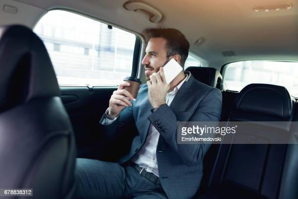 Successful businessman in a car using mobile phone.
