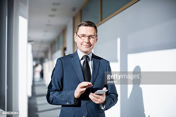 Successful businessman in office with mobile phone