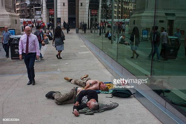 A successful businessman looks with pity at two men passedout and sleeping on the ground near Pudding lane the location of the Great Fire of London...