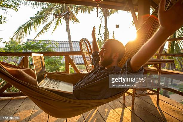 Successful businessman on hammock with computer-Sunset