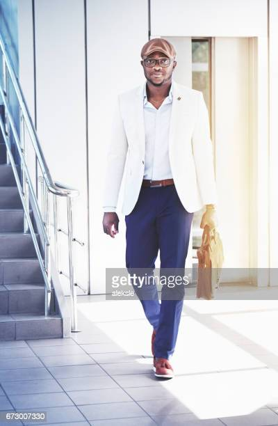 Succesvolle zakenman. Portret van een gelukkig lachend Afrikaanse zakenman in brillen wandelen op moderne kantoorgebouwen