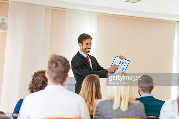 Successful businessman showing charts to seminar participants