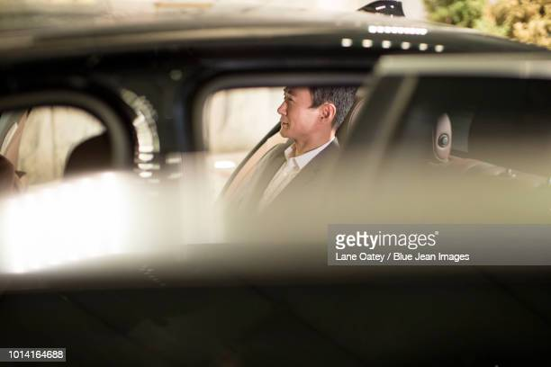 successful businessman sitting in car back seat - prestige car stock pictures, royalty-free photos & images