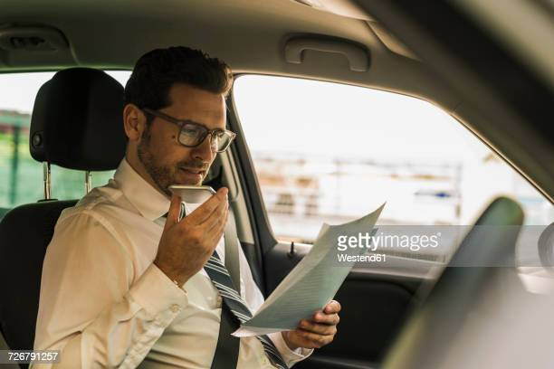 Successful businessman sitting in car reading files and using smartphone