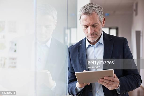 successful businessman standing in his office holding digital tablet - vestimenta de negocios fotografías e imágenes de stock