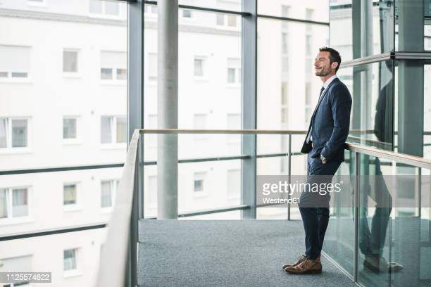 successful businessman standing in office building, looking out of window, daydreaming - lehnend stock-fotos und bilder