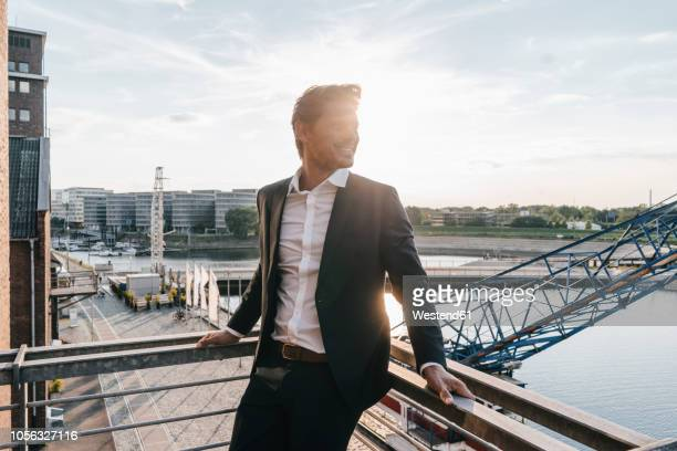 successful businessman standing on balcony - ruhr stock pictures, royalty-free photos & images